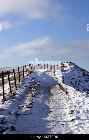 Path leading along Rushup Edge with a light dusting of snow in late afternoon mid winter light - Stock Photo