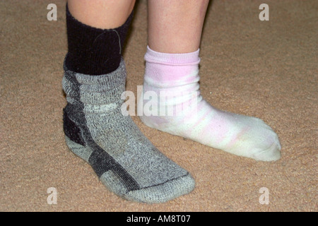 Teenagers feet with odd socks - Stock Photo