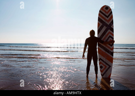 Man standing on beach with surfboard. - Stock Photo