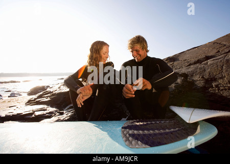 Couple sitting on beach with surfboard smiling. - Stock Photo
