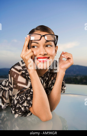 Woman pushing eyeglasses up onto head smiling outdoors. - Stock Photo