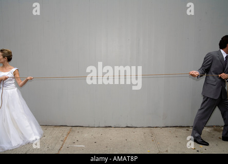 A bride and groom pulling a rope in different directions - Stock Photo