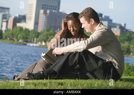 Mid adult couple sitting in a park reading a book, Boston, Massachusetts, USA - Stock Photo