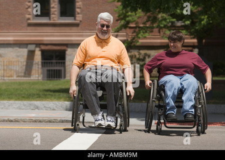 Middle-aged man and a middle-aged woman crossing a road in wheelchairs - Stock Photo
