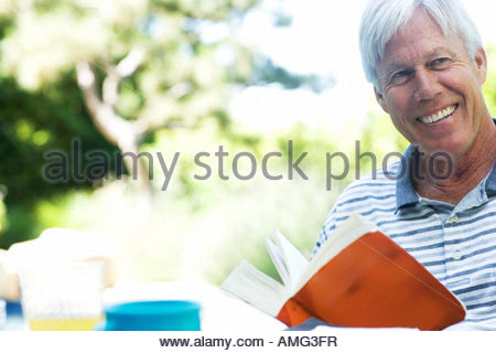 Man with book outdoors smiling - Stock Photo