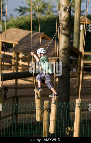 PICTURE CREDIT DOUG BLANE Young boy crossing a log bridge at the Aerial Extreme Willen Lake Milton Keynes City of - Stock Photo