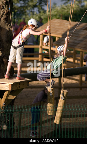 Young girl helping a boy cross a log bright at the Aerial Extreme Willen Lake Milton Keynes City of Milton Keynes - Stock Photo