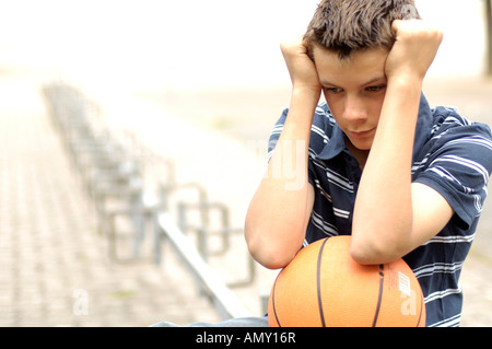 Close-up of teenage boy looking serious and holding basketball - Stock Photo