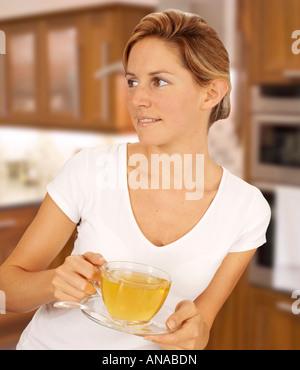 WOMAN IN KITCHEN DRINKING HERBAL TEA - Stock Photo