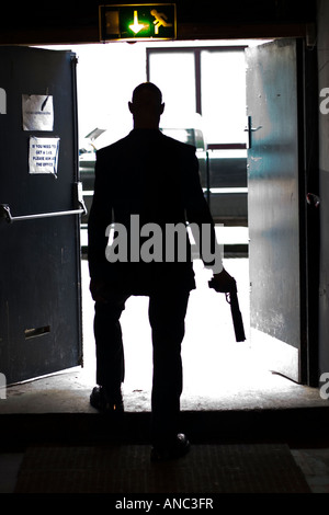 Silhouetted figure steps through doorway onto street with gun in hand - Stockfoto