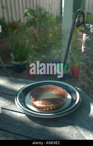 Pear and chocolate tartlet with table and chairs in spring garden setting - Stock Photo