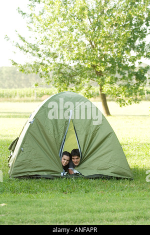Young campers peeking heads out of tent - Stock Photo