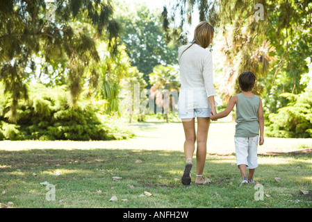 Mother and son, walking hand in hand, rear view - Stock Photo