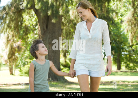 Mother and son, walking hand in hand, smiling at each other - Stock Photo