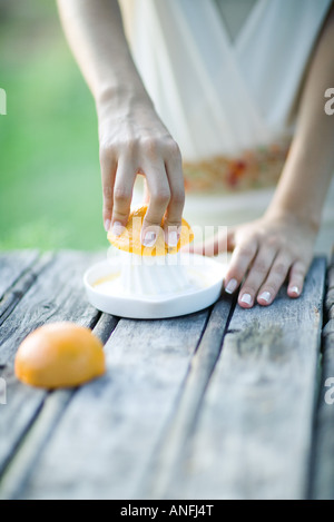 Woman pressing orange with citrus press, close-up, cropped view of hands - Stock Photo