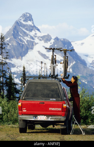 a young woman taking a mountain bike of the roofrack of a truck, just before venturing out on the Keystone-Standard - Stock Photo
