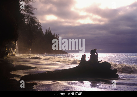 Person sitting on a log watching a storm roll in at Mystic Beach on the Juan de Fuca marine trail, British Columbia, - Stock Photo