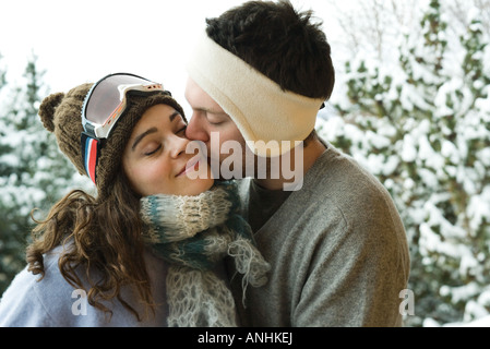 Young couple in winter clothing, man kissing woman on cheek - Stock Photo