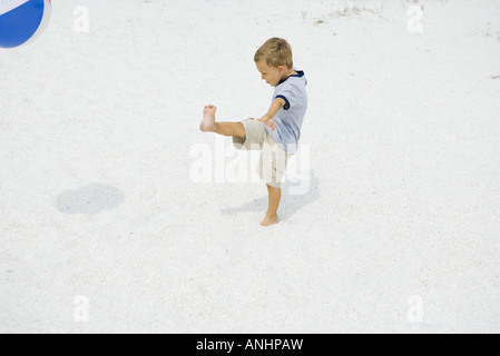 Young boy kicking beach ball at the beach, side view - Stock Photo