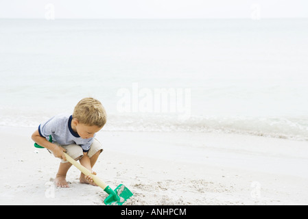 Young boy crouching at the beach, digging in sand with shovel - Stock Photo