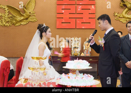 Bride and groom standing face to face, looking at each other, groom speaking into microphone - Stockfoto