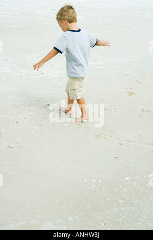 Little boy walking on beach with arms out, full length - Stock Photo