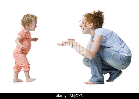 Profile of a baby girl reaching for her mother - Stock Photo