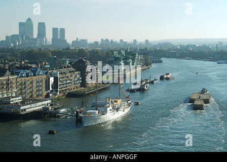 The Royal Yacht HNOMY KS Norge of the King Of Norway moored alongside HMS President Canary Wharf beyond with river - Stock Photo