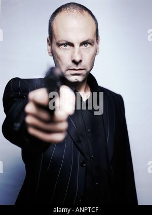 Gangster holding a gun - Stock Photo