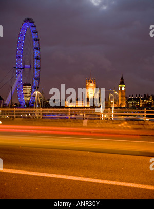 motion blur effect of light trails of traffic at night on Waterloo Bridge with Houses of parliament backdrop - Stock Photo