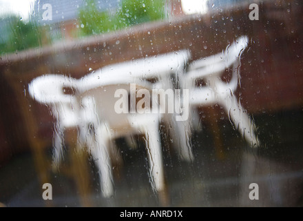 Patio furniture in the rain.  Seen through a rain spattered window. - Stock Photo