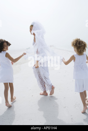 Bride and flower girls running on beach - Stock Photo