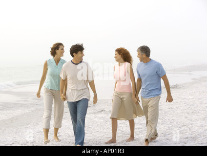 Two mature couples walking on beach, holding hands - Stock Photo