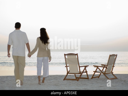 Newlyweds standing on beach, looking at view - Stockfoto