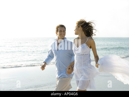Couple walking on beach, smiling at each other - Stockfoto