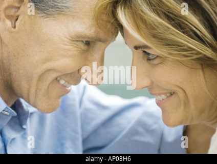 Mature couple looking at each other, foreheads together, close-up - Stock Photo