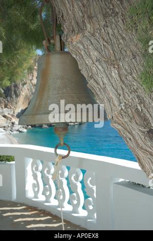 Europe, Greece, Karpathos, Kyra Panagia: church bell hanging in tree and Kyra Panagia chapel overlooking the beach - Stock Photo
