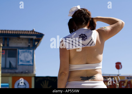 a chubby girl in a sailor outfit saluting at the mermaid parade in coney island - Stock Photo
