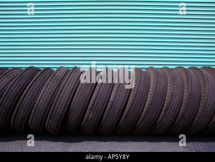 Warehouse Door Spare Tires Lined Up in a Row - Stock Photo