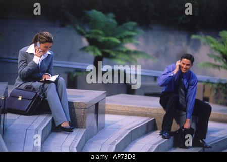Business people with cellphones and briefcases on steps in downtown Los Angeles - Stock Photo