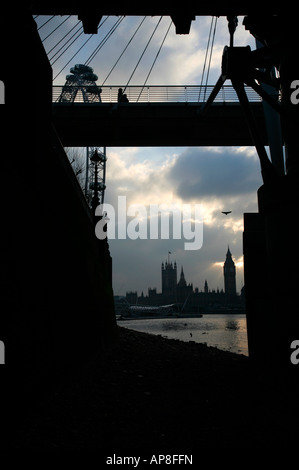 Houses of Parliament seen beyond London Eye and Golden Jubilee Footbridge, London - Stock Photo