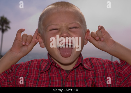 front teeth missing boy smiling sticking tongue out pulling on ears - Stock Photo