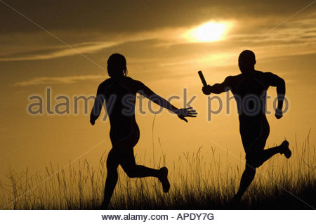 Male athletes running in relay race - Stock Photo