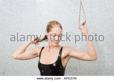 Woman in bathing suit taking shower - Stock Photo