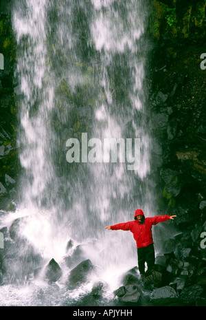 PICTURE CREDIT DOUG BLANE Carl Galvin in a red Mountain Equipment gore tex jacket under Svartifoss Waterfall in - Stock Photo