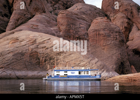 A houseboat moors in a cove surrounded by towering sandstone cliffs on Lake Powell - Stockfoto