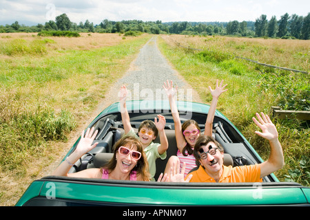 Enthusiastic silly family in convertible - Stock Photo