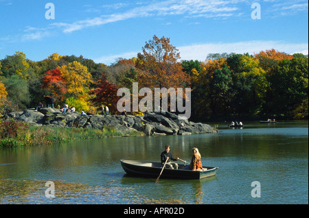 Couple in boat on lake during Fall Autumn in Central Park New York City USA - Stock Photo