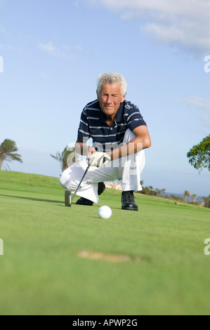 mature golf player kneeling by hole on puuting green - Stock Photo