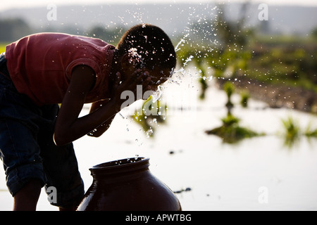 Silhouette of an Indian boy face washing from a clay pot next to of a rice paddy field. India - Stock Photo